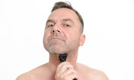 Man shaving his beard with a razor. Middle-aged man shaving his beard with a razor, isolated on white Royalty Free Stock Images
