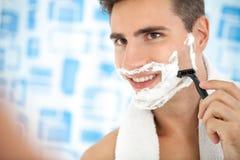 Man shaving his beard with razor. Young man shaving his beard with razor reflected on the bathroom's mirror Royalty Free Stock Photography