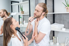Man shaving his beard while woman applying face powder in bathroom. Man shaving his beard while women applying face powder in bathroom in the morning Stock Photography