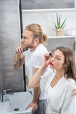 Man shaving his beard while woman applying mascara in bathroom Royalty Free Stock Photography