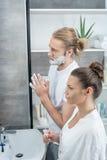 Man shaving his beard while woman brushing teeth in bathroom. Man shaving his beard while women brushing teeth in bathroom in the morning Stock Photo