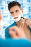 Man shaving his beard. Young man shaving his beard with a razor in bathroom Royalty Free Stock Photography