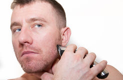 A Man Shaving His Face. With an electric beard trimmer Stock Images