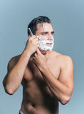 Man shaving his face getting ready for the day Stock Image