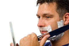 Man is shaving his face with knife Royalty Free Stock Photography