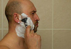 Man shaving his face with the razor blade through shave foam. Men skin care concept. Stock Photo