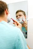 Man shaving his face, reflection in mirror Royalty Free Stock Photography