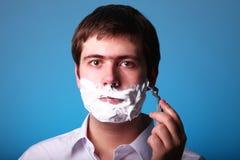 Man shaving isolated on blue background Stock Photography