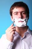 Man shaving isolated on blue background Stock Photos