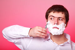 Man shaving isolated on red background Royalty Free Stock Image