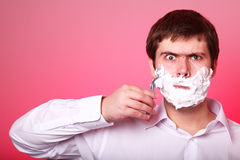 Man shaving isolated on red background Royalty Free Stock Images
