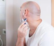 Man shaving. Before the mirror royalty free stock photo