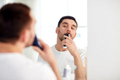 Man shaving mustache with trimmer at bathroom Stock Photos