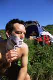 Man shaving in the outdoors next to tent Royalty Free Stock Images