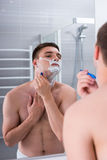 Man shaving with a razer and looking at the mirror in the bathro Stock Image