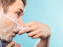 Man shaving with razor face profile Royalty Free Stock Photo