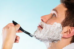 Man shaving with razor face profile. Health beauty and skin care concept. Closeup young bearded man with foam on face shaving with razor on blue background stock photography