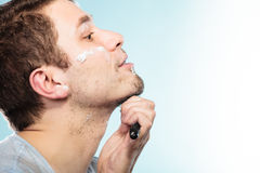 Man shaving with razor face profile Royalty Free Stock Images