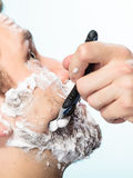 Man shaving with razor face profile Stock Photo
