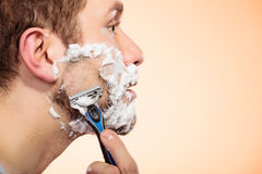 Man shaving with razor. Health beauty and skin care concept. Closeup young bearded man with foam on face shaving on bright orange background Royalty Free Stock Image