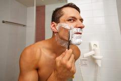 Man shaving razor. Unhappy man shaved half of his face Stock Photos