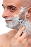 Man shaving with a razorblade stock photography
