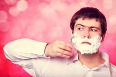 Man shaving  on red background Royalty Free Stock Images