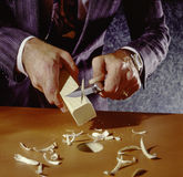 Man shaving square peg to fit round hole. In table Royalty Free Stock Images