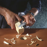 Man shaving square peg to fit round hole royalty free stock photo