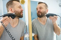 Man shaving trimming his beard stock photography