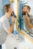 Man shaving trimming his beard. Bearded man looking at himself in mirror trimmng, shaving his beard using electric timmer razor stock image