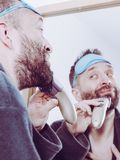 Man shaving trimming his beard. Bearded man looking at himself in mirror trimmng, shaving his beard using electric timmer razor. Guy taking care of facial hair royalty free stock photo