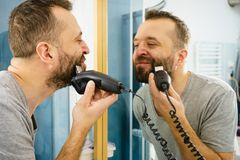 Man shaving trimming his beard royalty free stock images