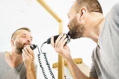 Man shaving trimming his beard. Bearded man looking at himself in mirror trimmng, shaving his beard using electric timmer razor royalty free stock photography