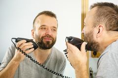 Man shaving trimming his beard. Bearded man looking at himself in mirror trimmng, shaving his beard using electric timmer razor stock photography