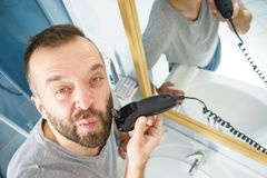 Man shaving trimming his beard. Bearded man looking at himself in mirror trimmng, shaving his beard using electric timmer razor royalty free stock photo