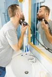 Man shaving trimming his beard. Bearded man looking at himself in mirror trimmng, shaving his beard using electric timmer razor stock photos