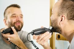 Man shaving trimming his beard. Bearded man looking at himself in mirror trimmng, shaving his beard using electric timmer razor stock photo