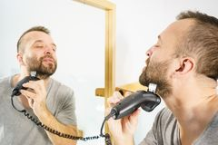 Man shaving trimming his beard. Bearded man looking at himself in mirror trimmng, shaving his beard using electric timmer razor royalty free stock photos