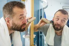 Man shaving trimming his beard. Bearded man looking at himself in mirror trimmng, shaving his beard using electric timmer razor royalty free stock images