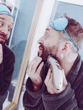 Man shaving trimming his beard. Funny mature adult man looking at himself in mirror trimmng, shaving his beard using electric timmer razor royalty free stock image