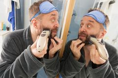 Man shaving trimming his beard. Funny mature adult man looking at himself in mirror trimmng, shaving his beard using electric timmer razor royalty free stock photography
