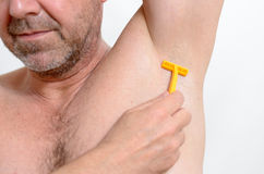 Man shaving under his armpit Royalty Free Stock Images