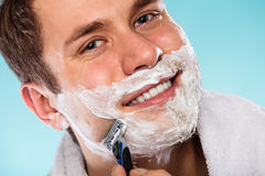 Man shaving using razor with cream foam. Royalty Free Stock Image