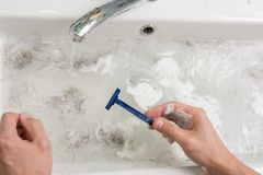The man is shaving, view of the hands with a razor and the wash basin with dirty water Stock Images