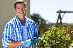 Man shearing shrub. Happy happy man shearing shrub at home garden Stock Images