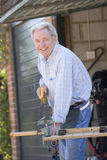 Man at shed sawing wood and smiling. At camera Stock Photo