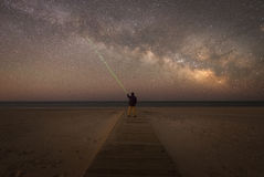 Man shining green laser to point at a star in the sky. A man at the beach observing the Milky Way Galaxy while point to a star with a green laser pointer Royalty Free Stock Image