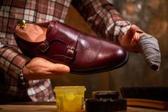 Man shining shoes with a rag. Royalty Free Stock Photo