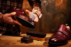 Man shining shoes with a rag. Stock Photos